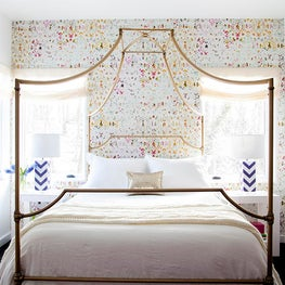 Little girl's room with accent wall, colorful printed wallpaper, gold canopy bed