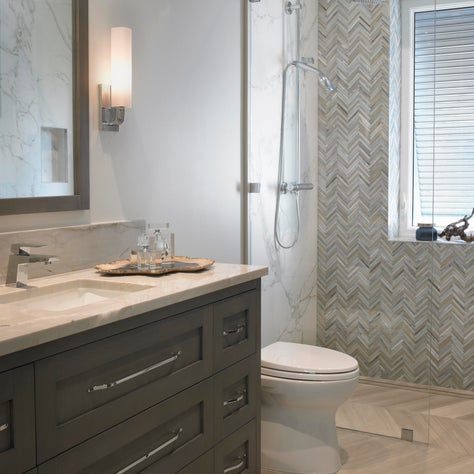 Warm wood vanity and gray tones zig zag floor to ceiling tiled shower.