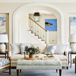 Blue and white coastal living room with rattan chairs and custom upholstery
