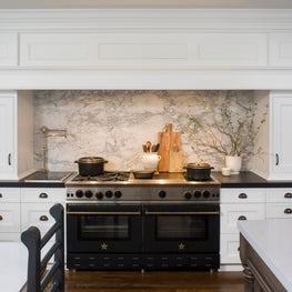 Mantel style hood that frames large cooking area, custom table and island.