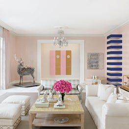 Living room in a limited palette of pale pink and white to complement the contemporary art collection