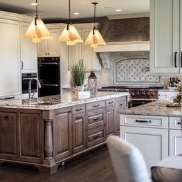 White kitchen with artsy pendants over wood-stained island; mosaic backsplash