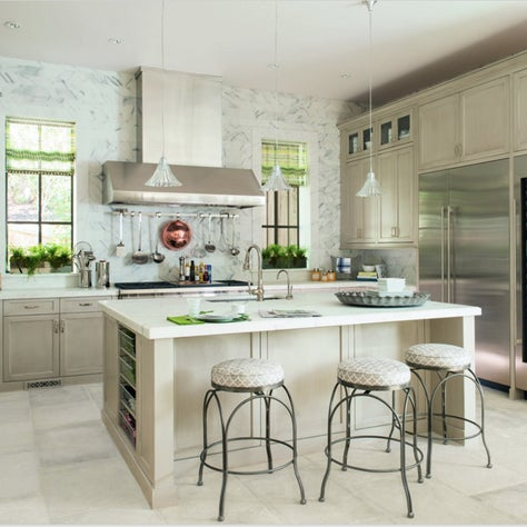 Sleek, bright kitchen with Calacatta Gold tiles covering the walls