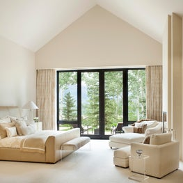 Bold windows and tall ceilings complete this master bedroom
