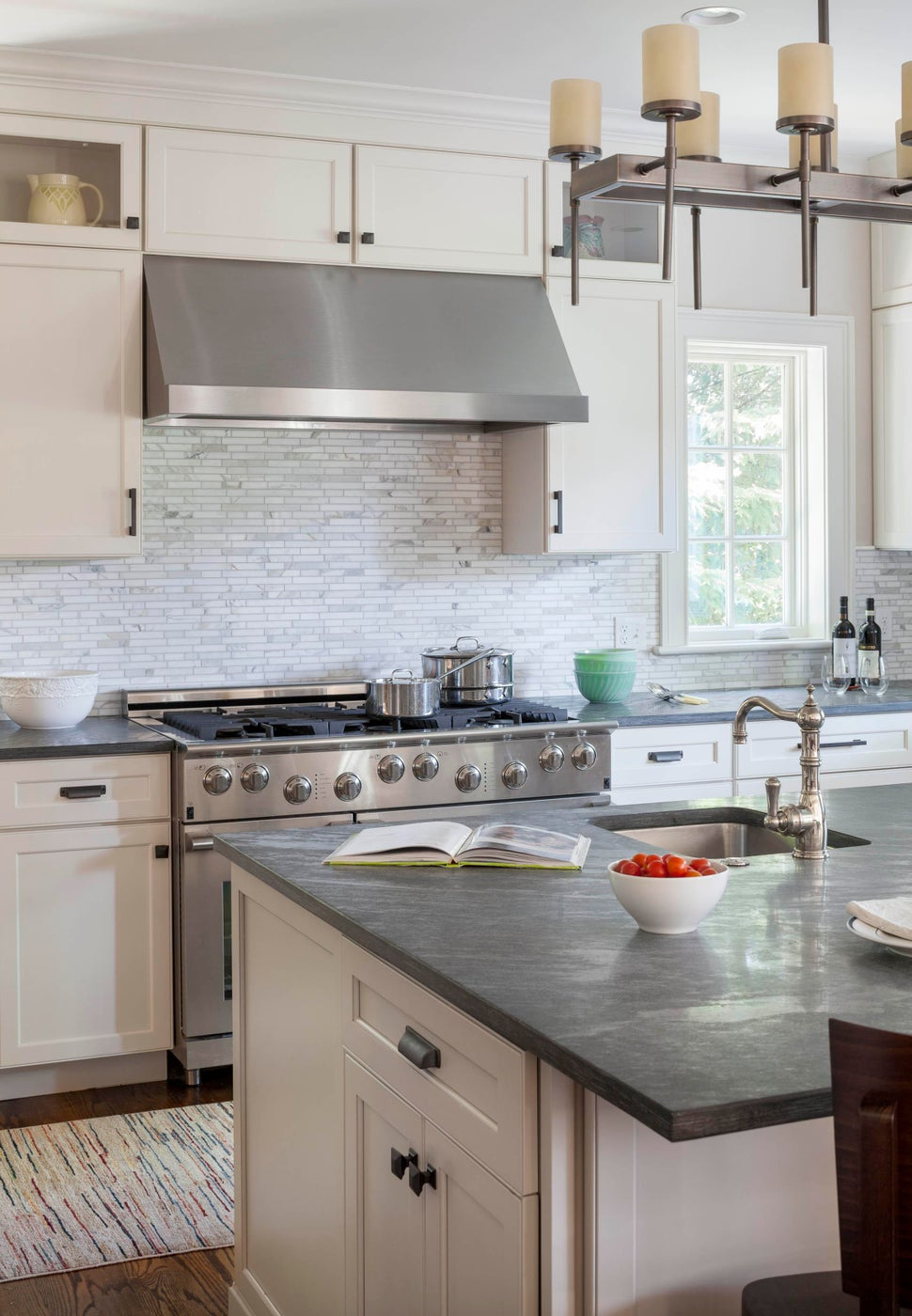 A steel range hood is softened by surrounding cabinets and textured backsplash