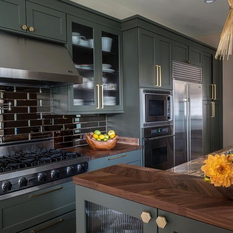 Rich Olive Green Kitchen With Gold Accents and Mirrored Subway Tile