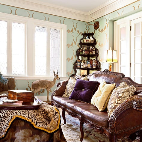 Gentleman's bar and library with hand stenciled walls, antiques, taxidermy, and layered rugs and fabrics by JIM THOMPSON.