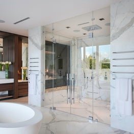 Marble walls surround this glass enclosed steam shower with a freestanding stone soaking tub, all have waterviews.