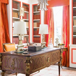 This glamorous library features lacquered walls in brilliant white & orange echoed by bright fabrics from Jim Thompson. Layers of books and antique furniture create a posh setting for the new neoclassicist. Designers: Summer Loftin and Marcia Sherrill