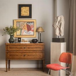 Design detail antique chest juxtapose to a Eames chair.
