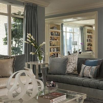 The color palette of creams and frosty blues create subtle shimmer as natural light illuminates the room.  The furniture, gathered around the fireplace, is upholstered a combination of cotton, linen, and bamboo, creating a cozy area within the cool room.