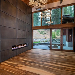 Rays of Light - ceiling-high steel fireplace surround panels, walnut plank flooring, glass chandelier and beamed ceiling
