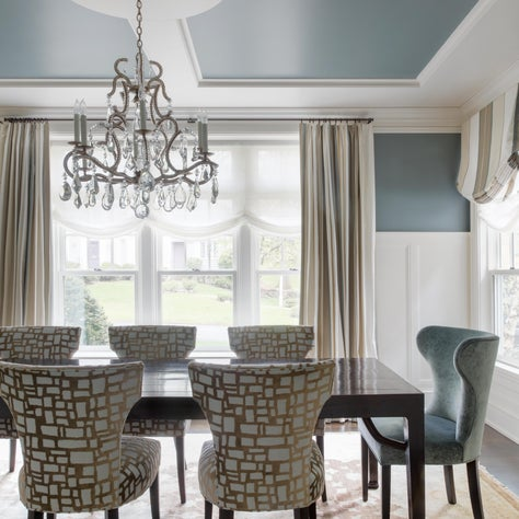 Painted ceiling detail and stunning chandelier make this dining room shine