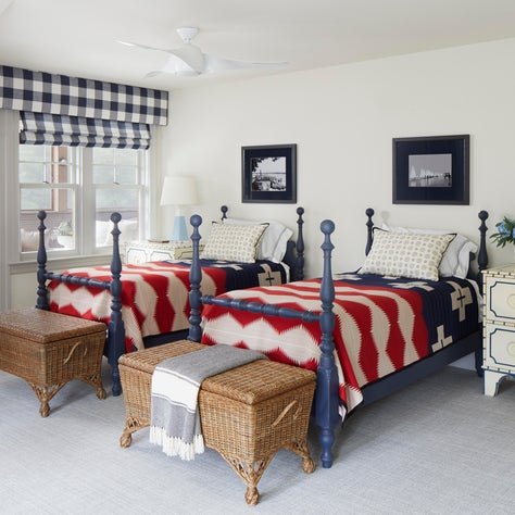 Red, white & blue camp blankets on navy 4 poster beds. Buffalo check shades.