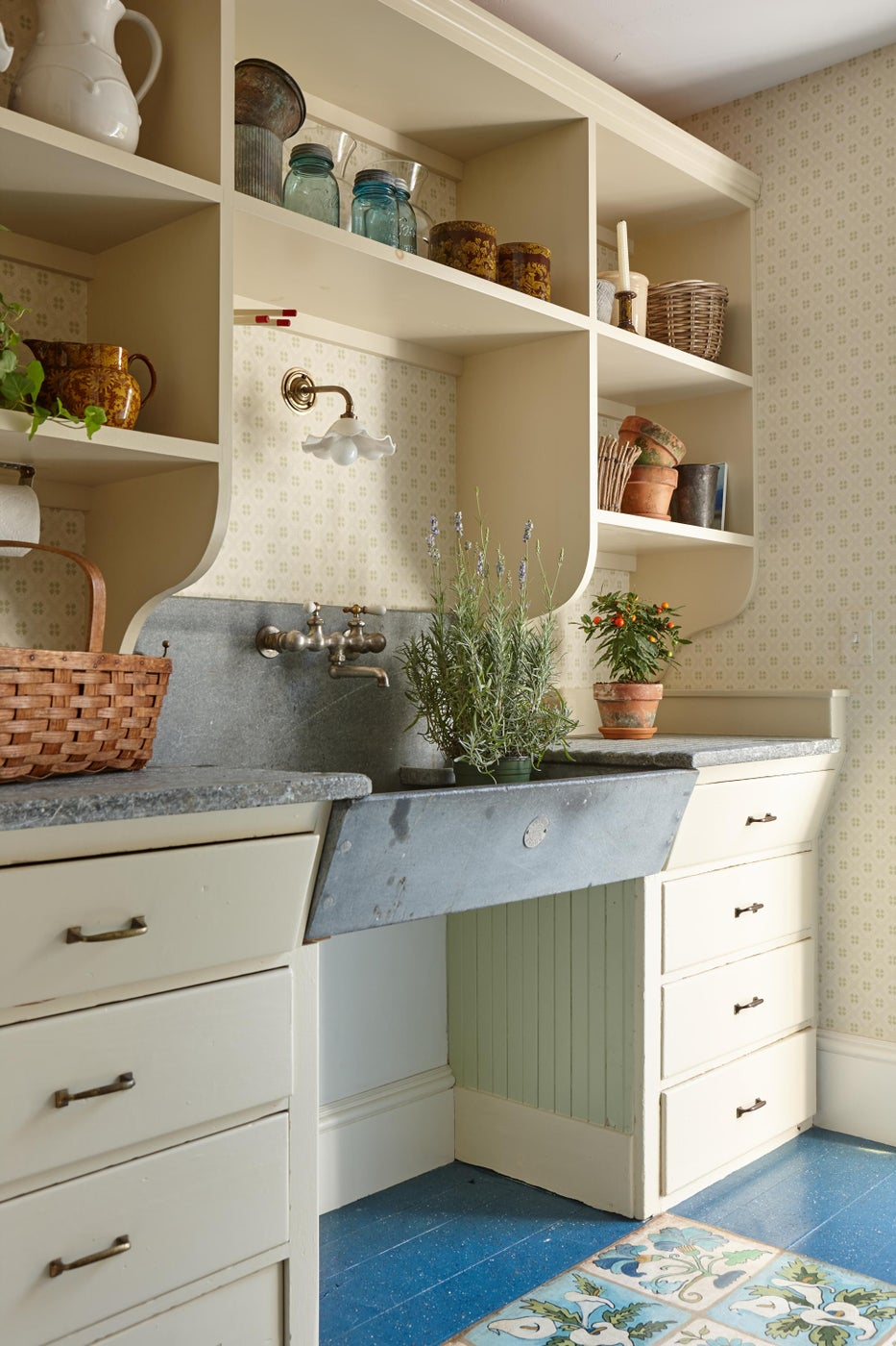 Flower room with antique soapstone sink and cabinets with splatter paint floor.