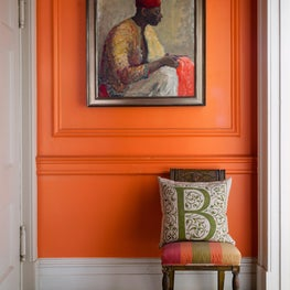 Entrance foyer with vibrant orange walls and mosaic floors
