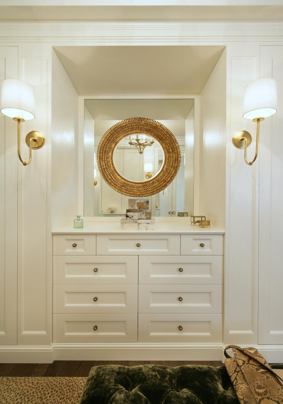 Dressing room designed with custom cabinetry and gold finishes