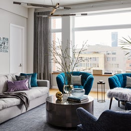 Luxe loft living in Boston's South End with stunning teal swivel chairs.