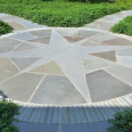 The large bluestone compass rose re-directs the main areas of the garden.