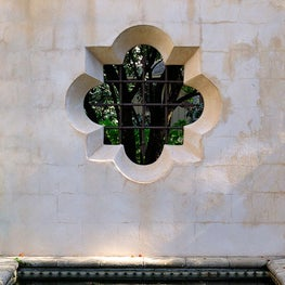Spanish Colonnial barbeb quatrefoil opening in a courtyard wall.