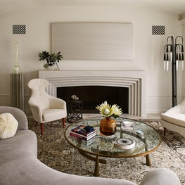 Living room with antique carpet and midcentury seating and floor lamp.