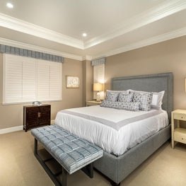 Master bedroom, custom bench with grey fabric cushion, grey and white bed and patterned bed pillows