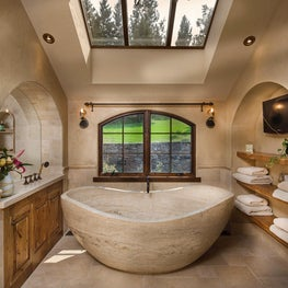Master bath with oversized freestanding tub, skylight, and archways