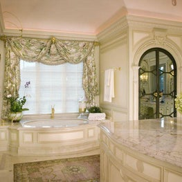 This opulent and ultra-feminine space provides a sumptuous bath for her as well as ample dressing room and office areas.