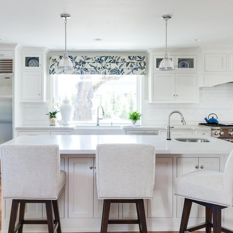 Kitchen island with swivel seating and traditional pendants with picture window