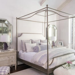 Luxurious lavender master bedroom, rubbed brass canopy bed, antique side tables