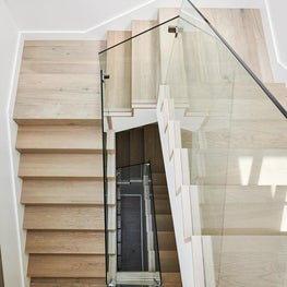 Bright stairs with light wood, white walls, and glass