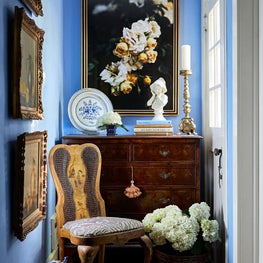 Cheerful hallway full of English antiques, chinoiserie, blue and white porcelains, and fabulous art! The periwinkle walls accented with warm gold tones pack in the charm in this historic home.