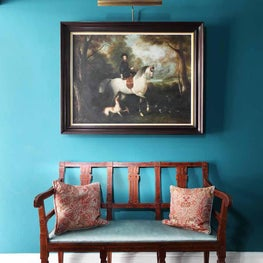 Colourful teal entrance hall with antique bench, rug and painting