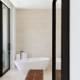 Neutral toned textured wall adds  layers to this serene bath.