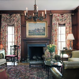 Formal paneled library with fireplace.