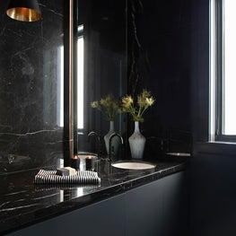 Dark and Moody powder with custom backlit mirror and black marble backsplash