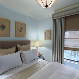 The blue-green walls blend in with the drapery fabric to create a soothing atmosphere
