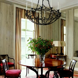 With faux-bois paneling and a whimsical forged iron chandelier by FW.