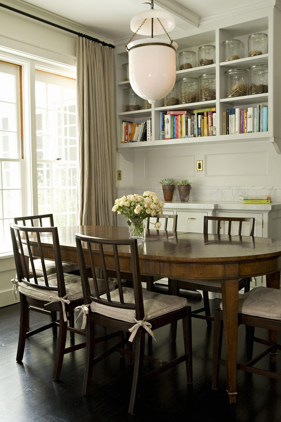 Breakfast room with built-in shelves, marble backsplash, and French doors