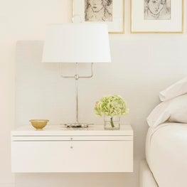 A custom wall mounted nightstand incorporated into the master headboard.