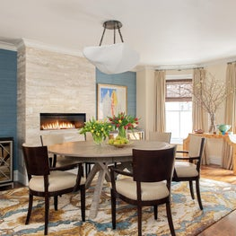 Traditional dining room chairs in contemporary room with stone-tiled fireplace