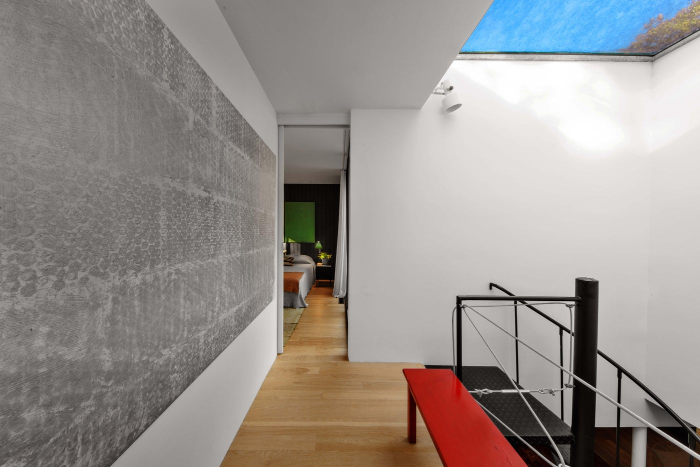 Clean modern hallway with skylight, red bench, large scale art