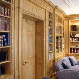 The library features traditional, hand-carved moldings and millwork.