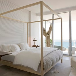 Bright master bedroom with driftwood repurposed as sculpture