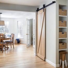 Natural oak barn door kitchen pantry with bronze hardware and breakfast room.
