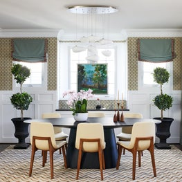 Wainscoting, grasscloth chandelier geometric zig zag rug walls blue drapes shade