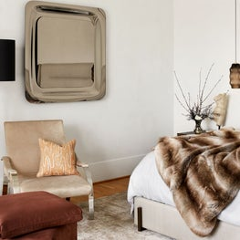 Warm primary bedroom with sitting area and artful pieces