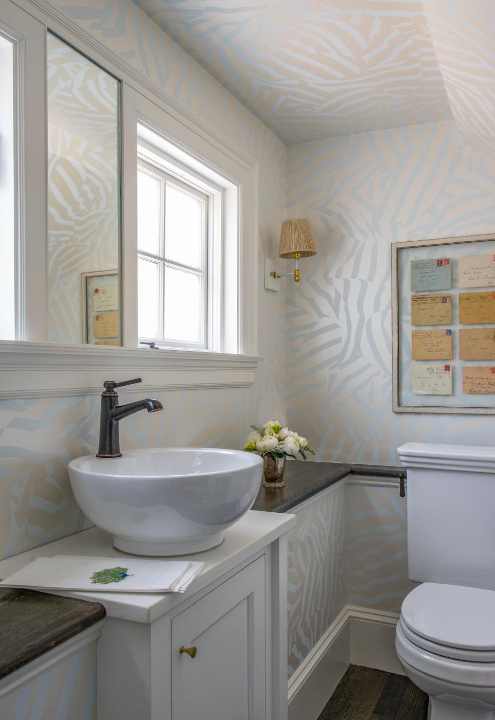 Wallpapered Bathroom with Ceramic Basin Sink and Letter Wall Art