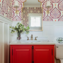 Colorful powder room bathroom with statement wallpaper white wainscot red vanity