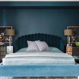 Art Deco Bedroom with teal walls, velvet bed, and mirrored nightstands